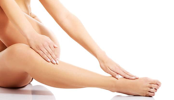 A woman caressing her smooth legs after waxing them in Tucson