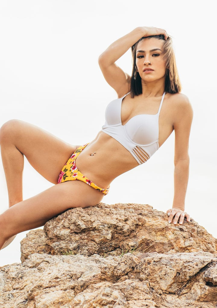 A woman posing on a rock in Tucson after getting waxed at The Waxing Studio A woman with a flawless look in a bikini after a bikini wax - The Waxing Studio